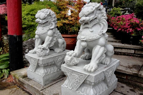 Outdoor Chinese stone lion fu dogs in front of house
